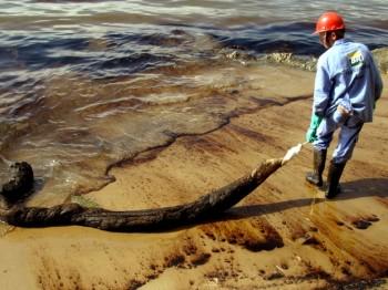 Funcionário da Petrobras duante o trabalho de remoção do óleo. (Foto: Reginaldo Pupo/ Estadão Conteúdo)